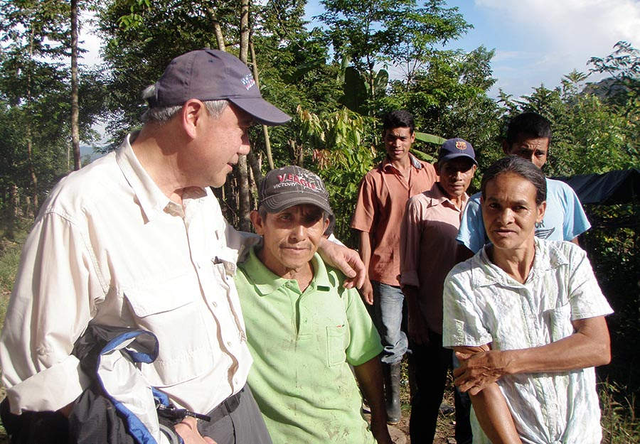 ELM partner Skip Li, left, visits with a couple who live in the village that ELM sponsors, Agroaldea San José.