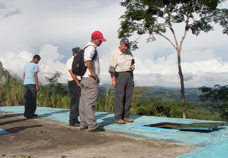 ELM partner Skip Li, right, looks at an irrigation tank in Agroaldea San José. ELM's sponsorship enabled Agros to install a new pump that carries water to the tank.