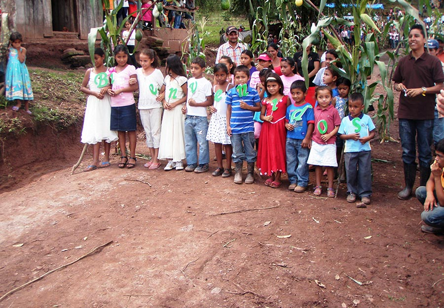 "Children from a village near Agroaldea San José greet ELM attorneys and their families with a sign that reads ""Bienvenidos"" – ""Welcome!"""